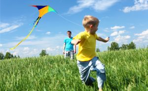 family flying kite on beautiful day